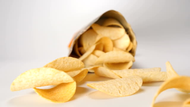 SLOW MOTION: Package falls and potato chips fall out from it SLOW MOTION: Package falls and potato chips fall out from it potato chip stock videos & royalty-free footage