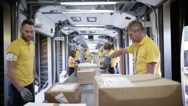 vídeos de stock e filmes b-roll de time-lapse pov package travelling on the conveyor belt and postal workers are sorting them - cardboard box