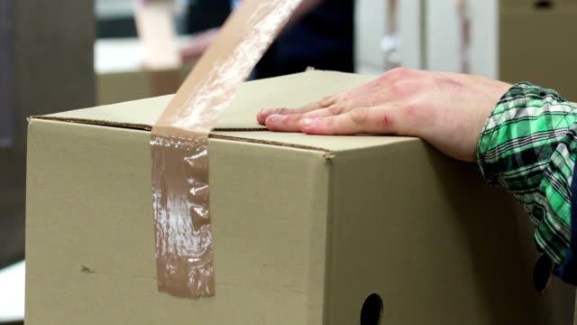 vídeos de stock e filmes b-roll de packaging a box for shipping - cardboard box
