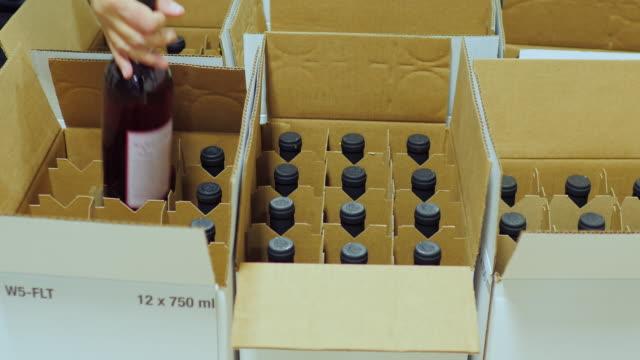 알코올로 포장 병입니다. 작업 골 판지 상자에 와인 병을 박 았 - 와인병 스톡 비디오 및 b-롤 화면