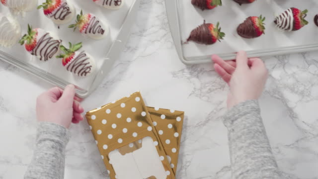 Packaging chocolate dipped strawberries into a paper box for a gift.