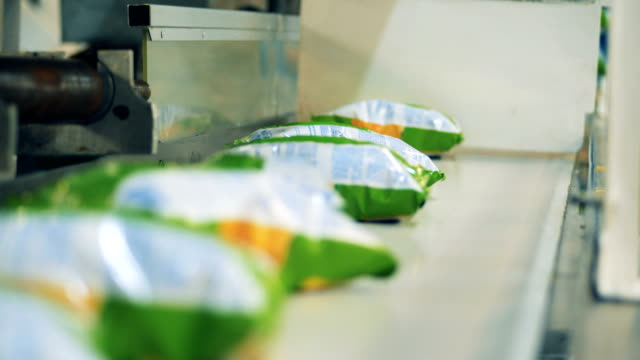 Packets of crisps are getting removed from the conveyor belt