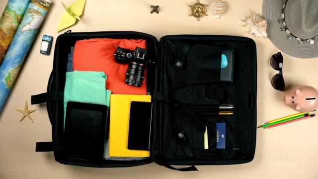 stockvideo's en b-roll-footage met het inpakken van een koffer, stop-motion. zich klaar voor de reis, vakantie. bovenaanzicht - ingepakt