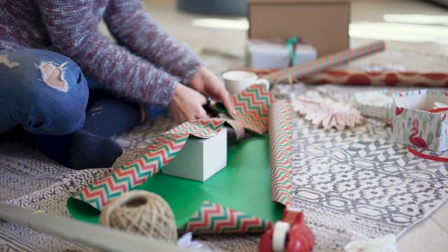 Packing Cube Box into Multicolored Modern Wrapping Paper Part of Beautiful Woman Wrapping Christmas Presents at Home wrapped stock videos & royalty-free footage