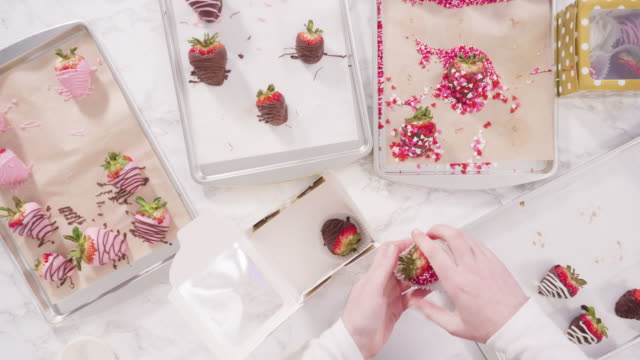 Packing gourmet chocolate dipped strawberries into a gift box.