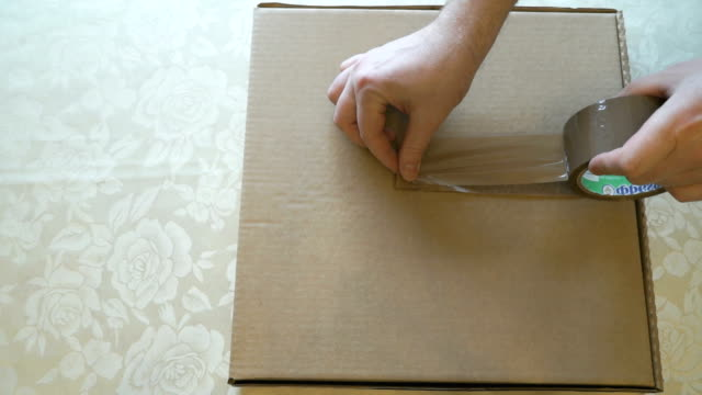 Packing the cardboard box of pizza using a scotch video
