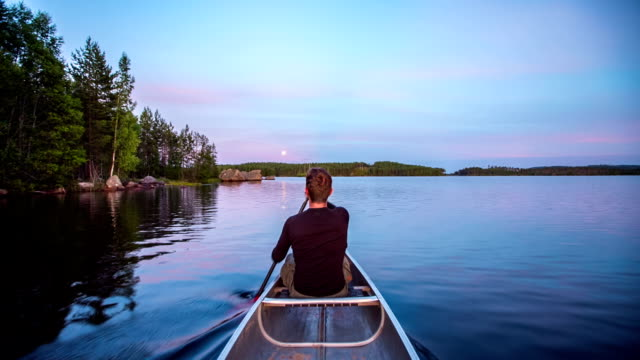 Paddling a Canoe on a lake in the wilderness POV video