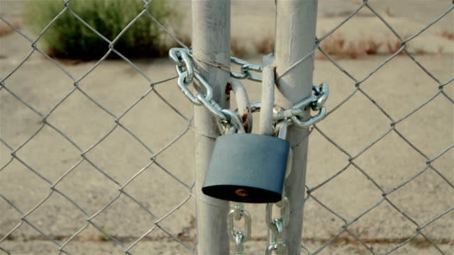 Padlock No entry via this padlocked chain linked fence gate. foreclosure stock videos & royalty-free footage