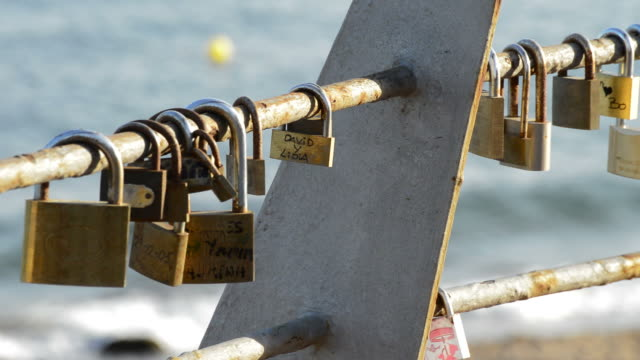 Padlocks with Names of Couples in Love at Sunset with Sea in the Background Padlocks with Names of Couples in Love padlock stock videos & royalty-free footage