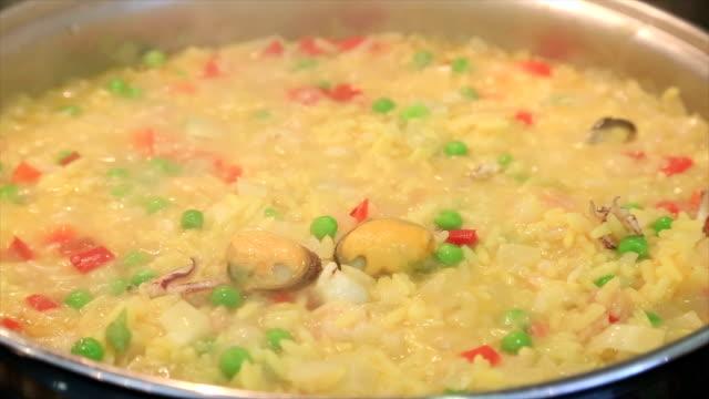 vídeos y material grabado en eventos de stock de paella se cocina en sartén - comida española