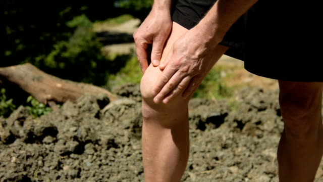 Pain in the knee. Problems with joints. Adult man outdoors. Healthy lifestyle. Pain and symptoms. knee stock videos & royalty-free footage
