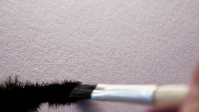 Paint brush painting black ink on white textured paper. Macro shot with amazing ink bleeds video