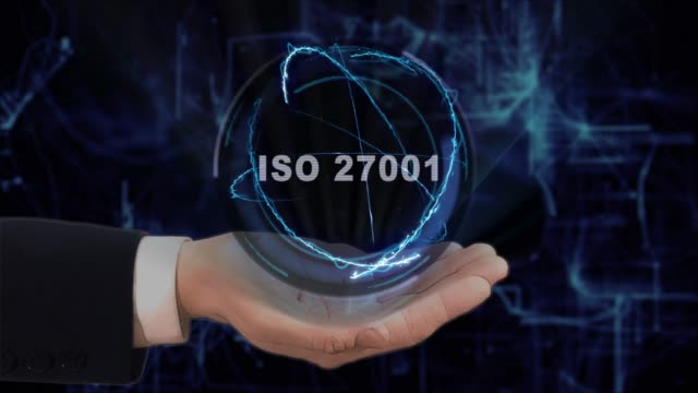 Painted hand shows concept hologram ISO 27001 on his hand