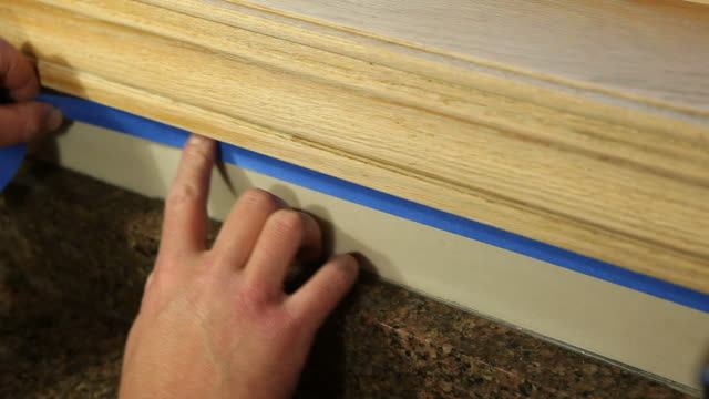 Painter Applying Blue Masking Tape to Protect Area video
