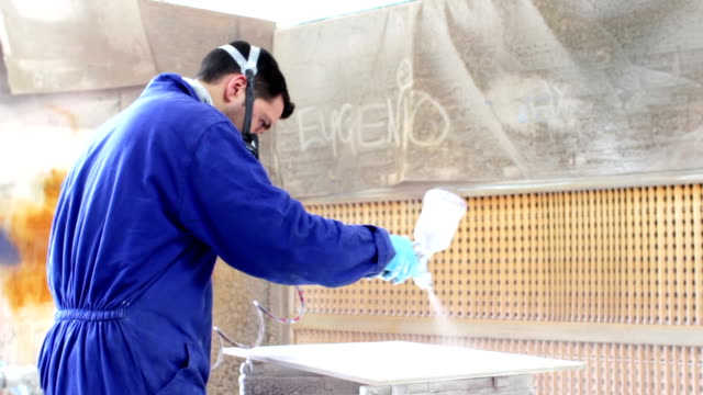 painter in a factory - industrial painting with airbrush (spray gun) - dolly video