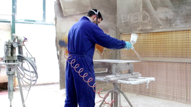 painter in a factory - industrial painting with airbrush - dolly video