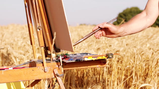 painter in the middle of a wheat field paints a beautiful landscape, canvas video