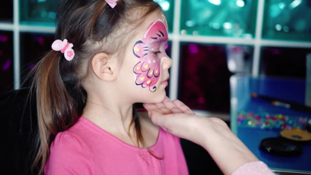 Painter makes butterfly shape at girl's face Painter hand draws face painting to little girl. Aqua makeup. Child with funny face painting. Medium close up. mask disguise stock videos & royalty-free footage