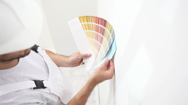 painter man at work choice color with swatches samples, wall painting concept, white copy space background video