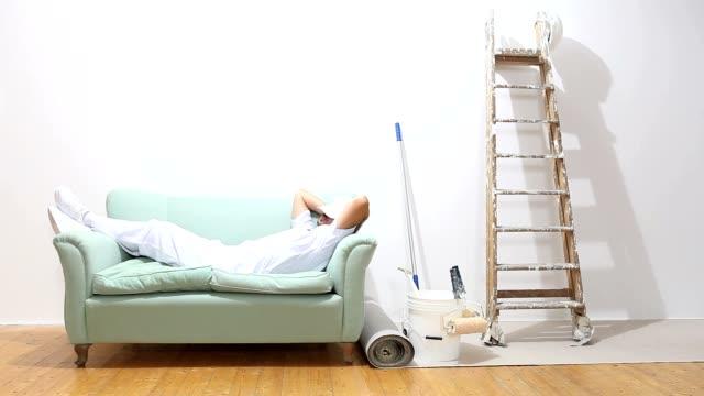pittore uomo al lavoro, lavoro ed è rifinita sul divano - pittore video stock e b–roll