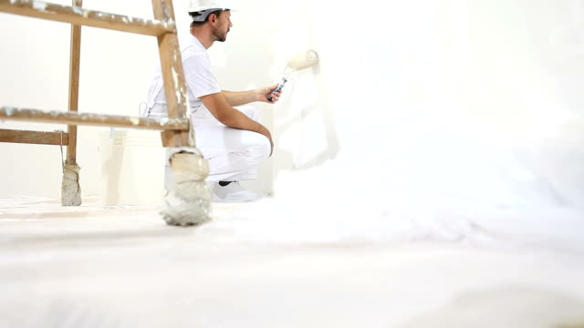 painter man at work, with roller painting wall, and wooden ladder in close up - painter stock videos and b-roll footage