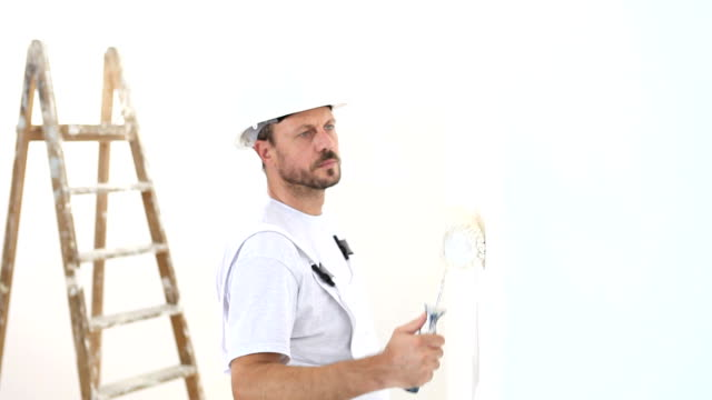 painter man at work, with roller painting wall, painter house concept video
