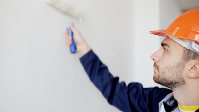 painter man at work, with roller painting wall painter man at work, painting wall house painter stock videos & royalty-free footage