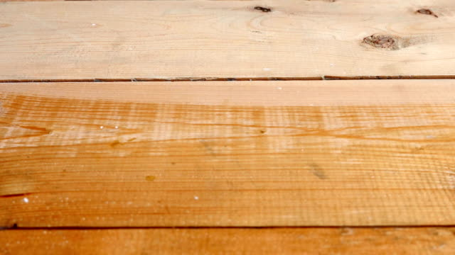 A painter painting with brush a wooden floor
