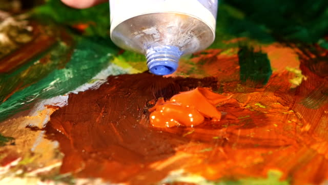 Painter squeezes blue oil paint on a palette, close up, slow motion Painter squeezes blue oil paint on a palette with other different colors like green, brown, orange, close up, slow motion canvas fabric stock videos & royalty-free footage