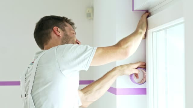 Painter using painters tape to protect the window from wall paint Professional painter using painters tape on the wall. Painter making a line on the wall he is about to paint. house painter stock videos & royalty-free footage