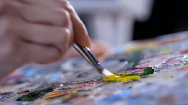 pittore con pennello che mescola vernice acrilica sulla tavolozza - tavolozza video stock e b–roll