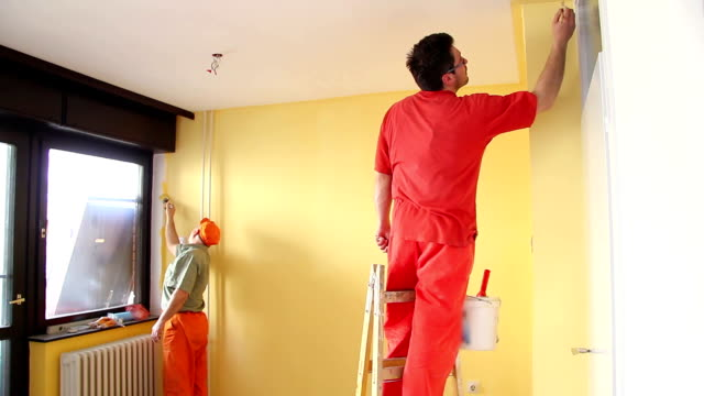 Painters in action Painters in action, senior man and young adult man on ladder painting the walls of the room with paint brush and roller, teamwork interior decoration house painter stock videos & royalty-free footage