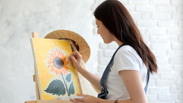 Painting a masterpiece Getting creative. Woman artist painting a sunflower at home canvas fabric stock videos & royalty-free footage