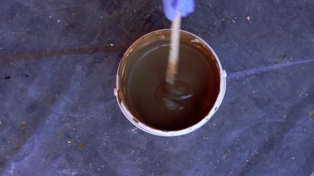vídeos de stock e filmes b-roll de painting and repairs - the paint in the bucket is stirred with a stick - castanho