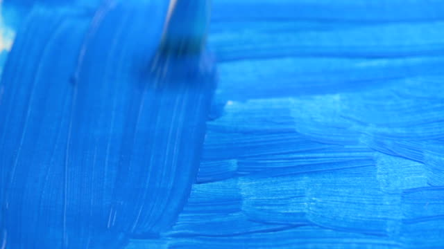 Painting blue color on paper full frame video