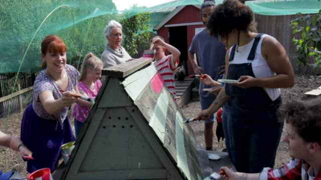 Painting Chicken Coop at Farm A group of people help paint the chicken coop at the farm. painting activity stock videos & royalty-free footage
