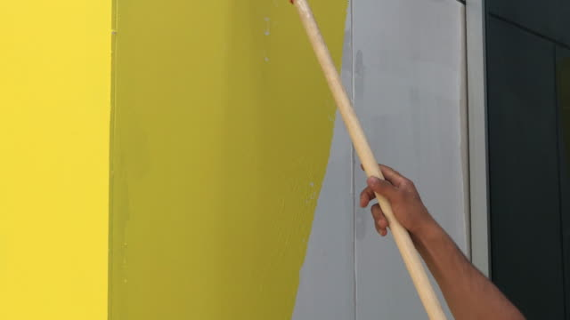 Painting hand with paintbrush yellow