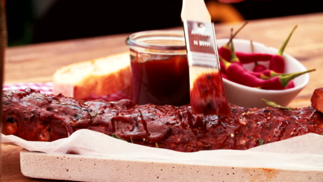 Painting marinade onto a rack of ribs with a cooking utensil video