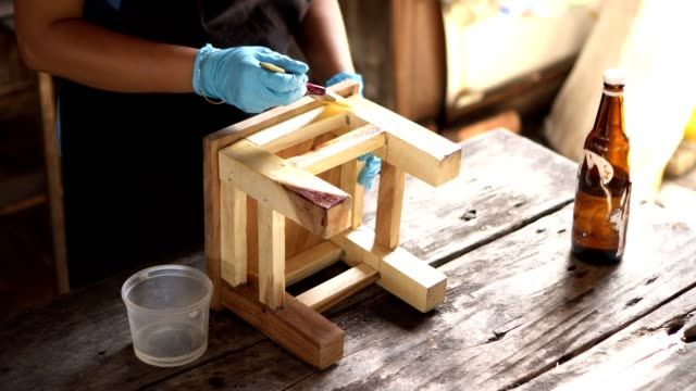 painting polyurethane wood chair - poliuretano polimero video stock e b–roll