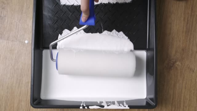 Painting the room with white paint, dipping a roller for painting with white paint.