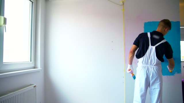 Painting The Wall Young Man Painting The Wall In Blue Color house painter stock videos & royalty-free footage