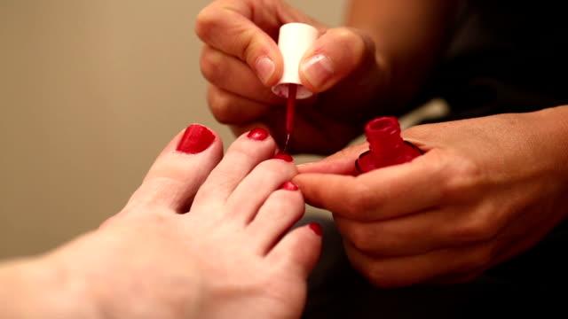 malować paznokcie u stóp zbliżenie nachylenie do dołu - pedicure filmów i materiałów b-roll