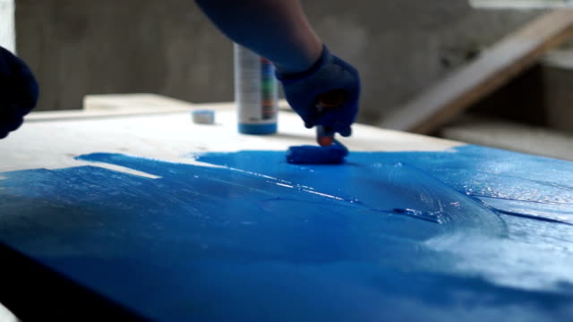 painting workshop the painter paints the plywood sheet blue painting art product stock videos & royalty-free footage