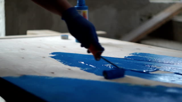 painting workshop the painter paints the plywood sheet blue mural stock videos & royalty-free footage