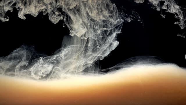 malt. abstrakte formen. schießen auf einem schwarzen hintergrund. - cappuccino stock-videos und b-roll-filmmaterial