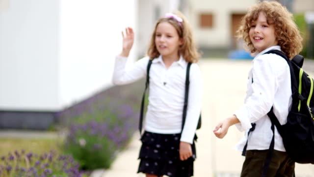un paio di scolari ricci, un ragazzo e una ragazza, salutano, agitando le mani, guardando la telecamera, si dispiegano e se ne vanno. addio scuola, torna a scuola - dorso umano video stock e b–roll