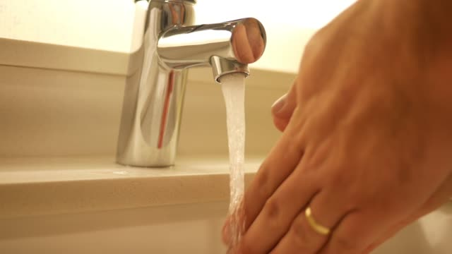 A pair of hands turn on running water in sink A pair of hands turn on running water in sink chlorine stock videos & royalty-free footage