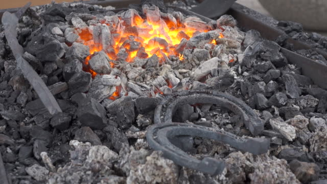 A pair of horseshoes cools in a forging brazier. Annealing and heat-treating of iron parts for forging. A pair of horseshoes cools in a forging brazier. Annealing and heat-treating of iron parts for forging. The camera moves from the  flame to the horseshoes. wrought iron stock videos & royalty-free footage