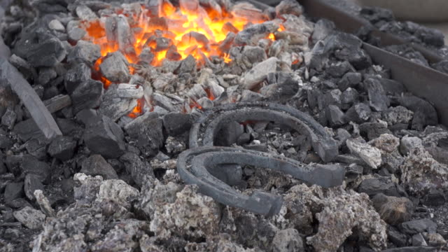 A pair of horseshoes cools in a forging brazier. A pair of horseshoes cools in a forging brazier. Annealing and heat-treating of iron parts for forging. The camera moves from the horseshoes to the flame. wrought iron stock videos & royalty-free footage