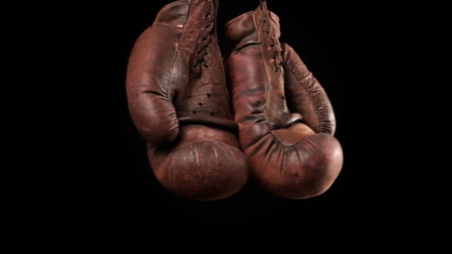 黒い背景にぶら下がっている革のヴィンテージ茶色のボクシンググローブのペア - スポーツ用品点の映像素材/bロール
